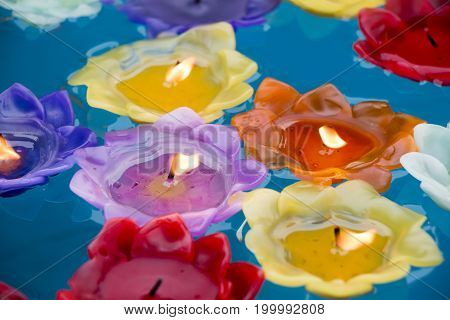 Colorful burning candles floating on blue water.
