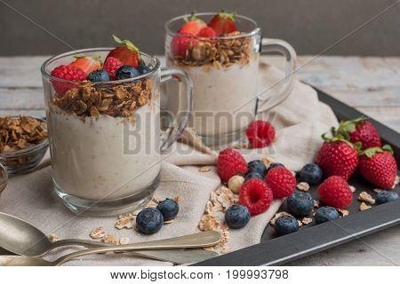 Breakfast parfait with homemade granola fresh fruits and yogurt.
