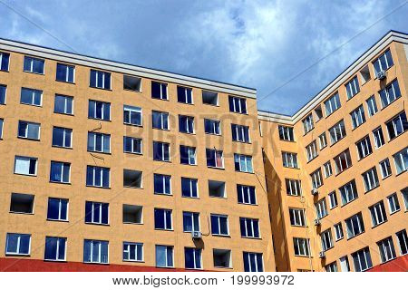 Facade of a large house with apartments and windows of brown color against a background of gray clouds
