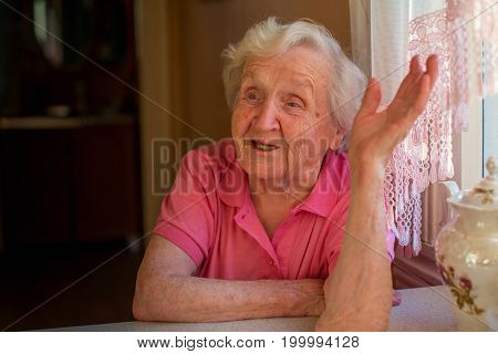 Elderly woman in red talking animatedly sitting at the table.