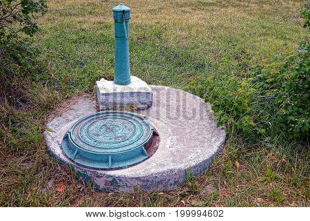 Old sewer hatch and column on concrete in the park
