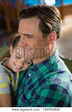 Close-up of cute daughter embracing father at home