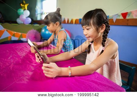 Little girls using tablet at party at home