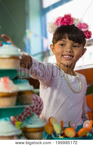 Girl having cupcake during birthday party at home