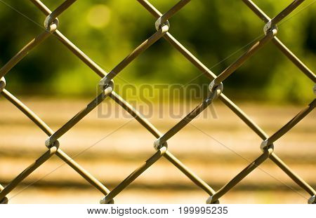 Closeup of a fence with a blurred rail background