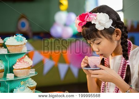 Cute girl drinking tea during birthday party at home
