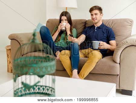 Young couple on the sofa drinking coffee while watching tv