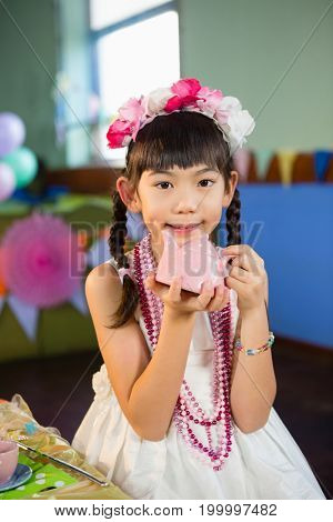 Portrait of cute girl holding toy teapot during birthday party at home