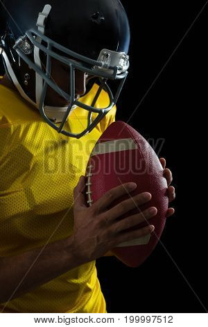 American football player holding a football with both his hands against black background