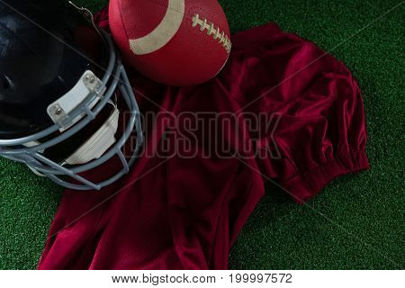 Close-up of American football jersey, head gear and football lying on artificial turf