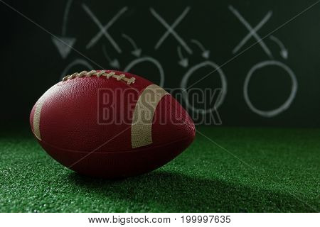 Close-up of American football lying on artificial turf against strategy board