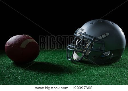 Close-up of American football head gear and football on artificial turf