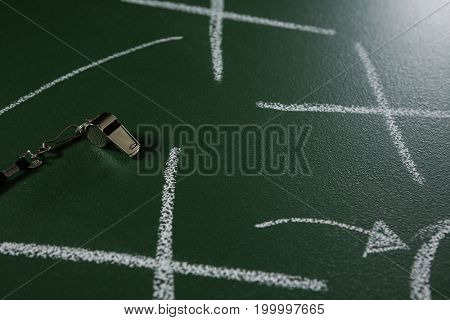 Close-up of referee whistle lying on green board with strategy drawn on it