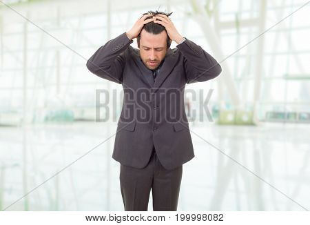 Businessman in a suit gestures with a headache, at the office