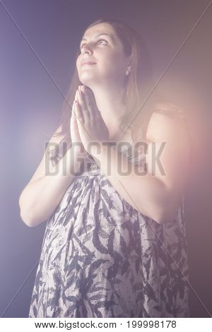 Portrait of Praying Pregnant Caucasian Female. Posing With Hands on Belly Against Black Background. Vertical Composition