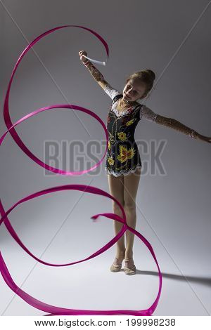Sport Concepts. High Contrast Portrait of Caucasian Female Rhythmic Gymnast In Professional Competitive Suit Doing Artistic Ribbon Spirals Exercises in Studio On White. Vertical Composition