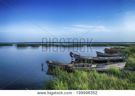 Scenic Destinations. Line of Boats on Water Placed in Belarussian National Park Braslav Lakes at Sunset during Summer Time. Horizontal Image Composition