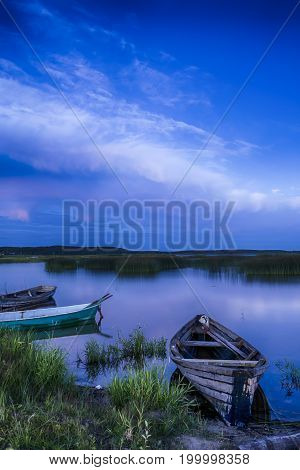Scenic Destinations. Line of Boats on Water Placed in Belarussian National Park Braslav Lakes at Sunset during Summer Time. Vertical Shot