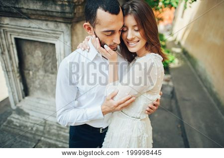 Beautiful young couple in love kissing on the street.