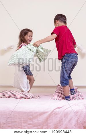 Funny Kids Playing with Pillows on Bedroom. Improvised Children Battel Indoors.Vertical Image Composition