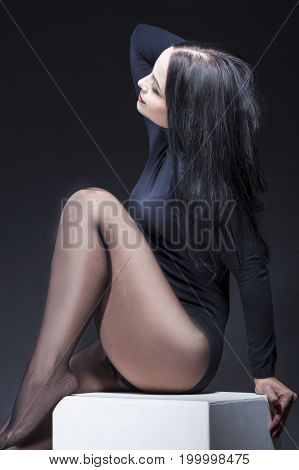 Portrait of Sensual Caucasian Brunette Posing in Black Body Suit on White Prop. Demonstrating Attractive Sexy Legs. Against Black Background. Vertical Image Composition