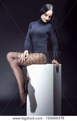 Portrait of Sensual Relaxing Caucasian Brunette Sitting in Black Body Suit on White Prop. Against Black Background. Vertical Image Composition