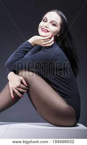 Portrait of Smiling Sexy and Alluring Caucasian Mature Brunette Woman in Black Body Suit. Posing Against Black Background.Vertical Composition