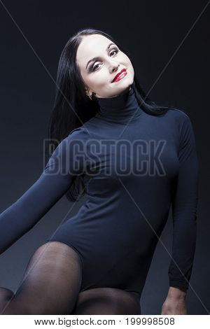 Beauty Ideas. Sexy and Sensual Alluring Caucasian Mature Brunette Woman in Black Body Suit. Posing Against Black. Vertical Image