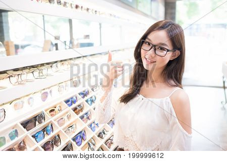 beauty woman wear eyeglasses and show thumb up to you in the store