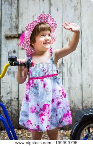 Three Years Old Girl Sending Regards With A Bicycle