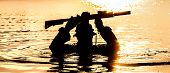 Silhouette of special forces with rifle in action during raid crossing river in the jungle waist deep in the water, with weapons over his head poster