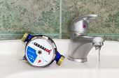 Not connected meter for consumption measuring of a cold water on a wash basin beside mounted handle mixer tap and water flowing from him on background of a wall with green tiles poster