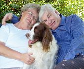 Couple and their dog english spaniel having a cuddle poster