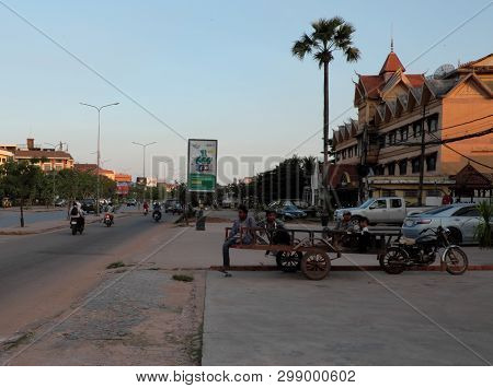 Siem Reap, Cambodia, December 17, 2018 Several Men Sit On A Cart. Direct City Street On Which Motor