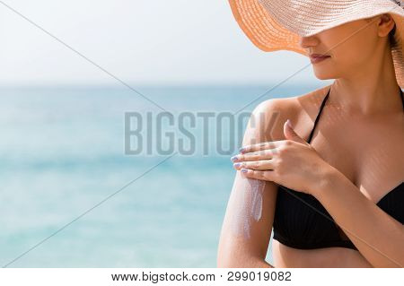 Sunscreen Sunblock. Woman In A Hat Putting Solar Cream On Shoulder Outdoors Under Sunshine On Beauti