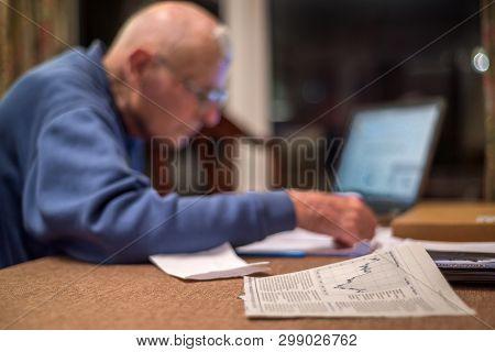 Elderly Pensioner Using A Computer To Check His Share Portfolios ,hampshire,england,u.k.