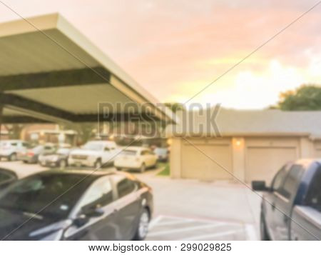 Blurry background typical apartment complex with detached garage and covered parking lots at sunset poster