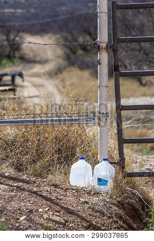 Vertical Shot Of Water Bottles Left Out For Migrants In The Arizona Desert
