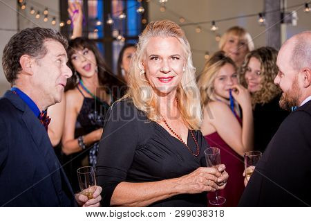 Attractive Mature Woman With Male Friends At A Party