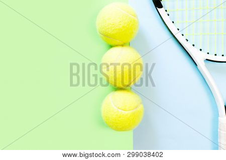Three Tennis Balls And White Racquet On Blue Background. Trendy Minimal Design Top View Pastel Colou