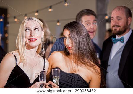 Two Pretty Women Reacting To A Couple Of Men At Party
