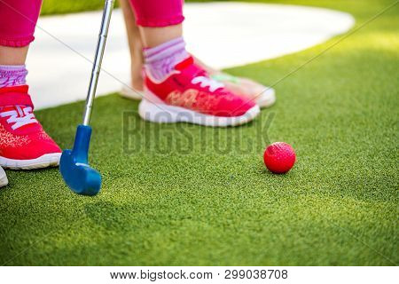 Miniature Golf Outdoor. Little Girl Hit Ball In The Mini Golf Course.
