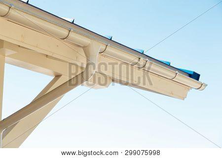 Gutter On House Corner. Metal Eave On Roof