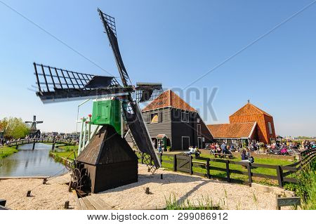 Zaanse Schans, Netherlands - 22 April 2019: Tourists sightseeng traditional Dutch rural houses and windmills in Zaanse Schans, is a typical small village within Amsterdam area.