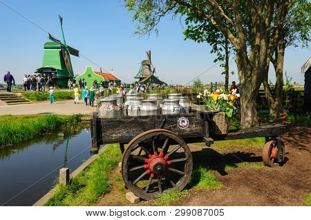 Zaanse Schans, Netherlands - 22 April 2019: Tourists sightseeng traditional Dutch houses in Zaanse Schans, is a typical small village within Amsterdam area. Retro milk cart at foreground.