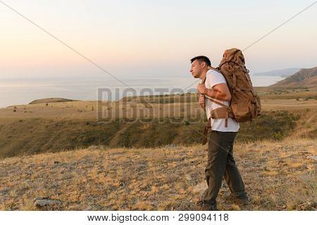 Tourist Puts On His Backpack In The Middle Of The Steppe