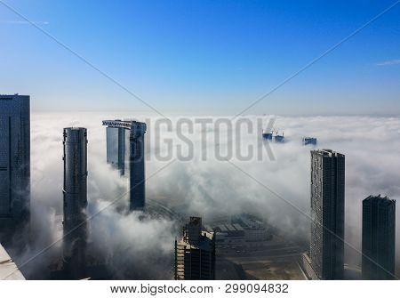Top Aerial View Shot Of Skyscrapers In The City With Fog Clouds Passing By - Abu Dhabi Al Reem Islan