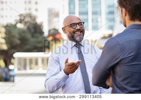 Smiling mature african businessman talking to his colleague outside the office. Two cheerful business men talking to each other. Mature man with in conversation with young colleague on street.