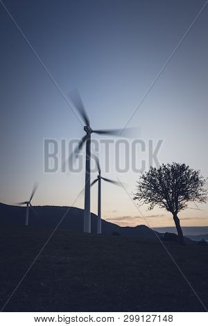 Rotating Windmill Generating Renewable Energy Wind Power At Land. Sustainability By Windmills Turbin