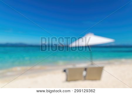 Out Of Focus Of  Sunbeds With Umbrella On The Sandy Beach Near The Sea. Summer Holiday And Vacation